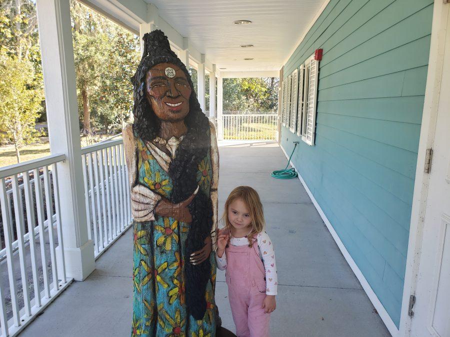 girl with folk art statue